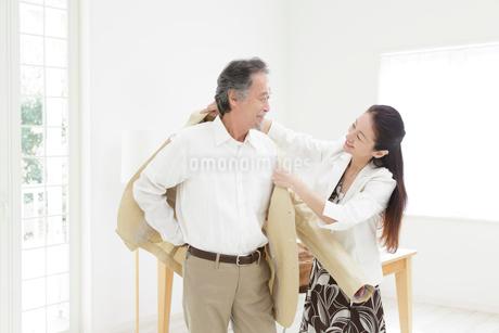 男性にジャケットを羽織らせる女性の写真素材 [FYI01906111]