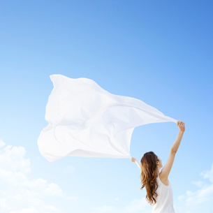 青空の下で布を持って広げる女性の写真素材 [FYI01906675]