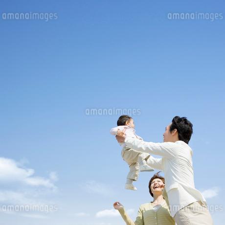子供を抱上げる父親と笑顔の母親の写真素材 [FYI01906928]