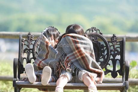 ブランケットに包まりベンチに座る姉妹の写真素材 [FYI01907046]