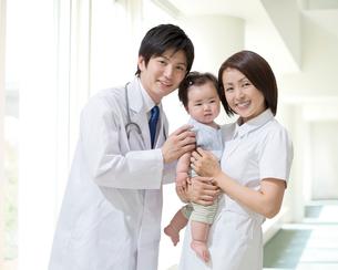 赤ちゃんを抱く看護師と医師の写真素材 [FYI01907558]
