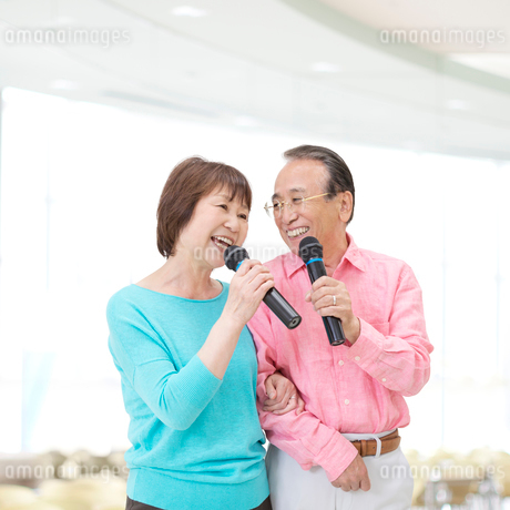 マイクを持って歌うシニア夫婦の写真素材 [FYI01907589]