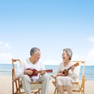 海辺でウクレレを弾くシニア夫婦の写真素材 [FYI01907591]