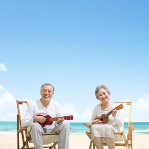 海辺でウクレレを弾くシニア夫婦の写真素材 [FYI01907722]