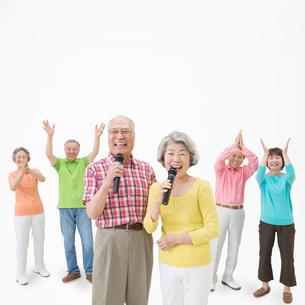 マイクを持って歌う男女と拍手するシニア男女達の写真素材 [FYI01907805]