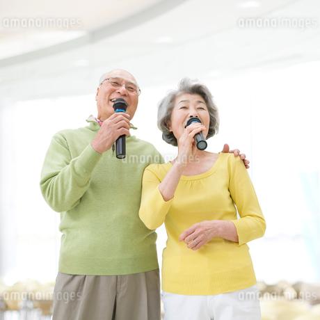 マイクを持って歌うシニア夫婦の写真素材 [FYI01907818]