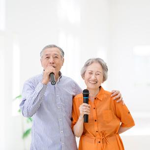マイクを持って歌うシニア夫婦の写真素材 [FYI01908044]