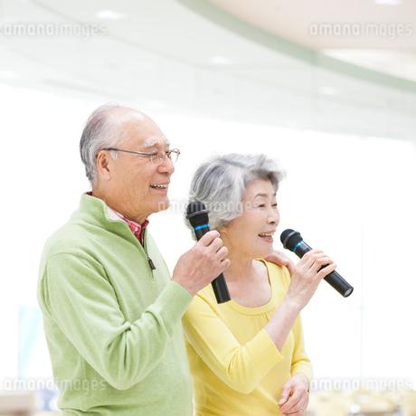 マイクを持って歌うシニア夫婦の写真素材 [FYI01908680]