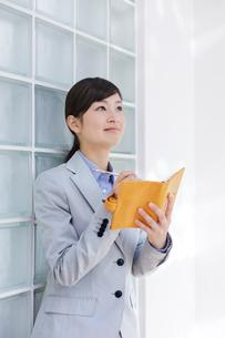 手帳にメモをする女性の写真素材 [FYI01908915]