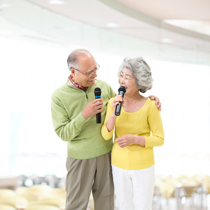 マイクを持って歌うシニア夫婦の写真素材 [FYI01908918]