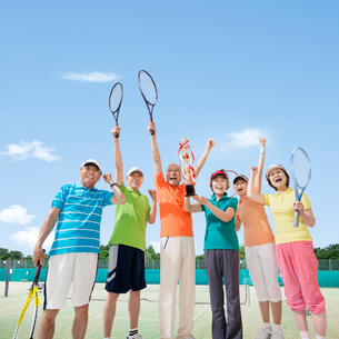 テニスラケットを持つシニア男女達とトロフィーを持つ女性の写真素材 [FYI01909034]