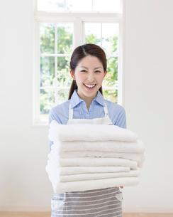 洗濯物を抱える女性の写真素材 [FYI01909571]