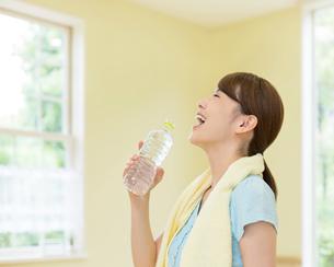 水の入ったペットボトルを持つ女性の写真素材 [FYI01909659]
