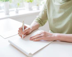 手紙を書くシニア女性の手元の写真素材 [FYI01910338]