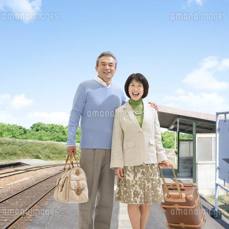 駅のホームに立つ笑顔の夫婦の写真素材 [FYI01910413]