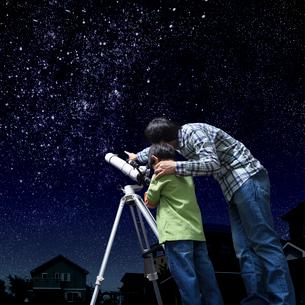 星空の下で望遠鏡を覗く父と息子の写真素材 [FYI01911133]