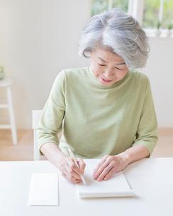 手紙を書くシニア女性の写真素材 [FYI01911177]