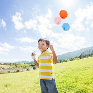 風船を持って立つ男の子の写真素材 [FYI01911425]