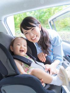 娘をチャイルドシートに乗せる母親の写真素材 [FYI01913063]