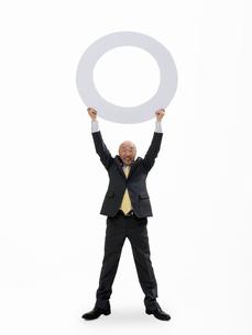 丸を持ち上げるビジネスマンの写真素材 [FYI01913566]