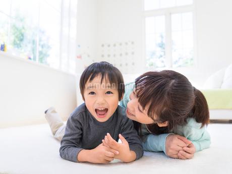 うつ伏せに寝転ぶ母と息子の写真素材 [FYI01913902]