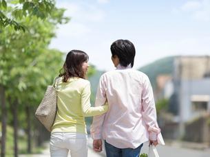 腕を組んで歩くカップルの写真素材 [FYI01913946]