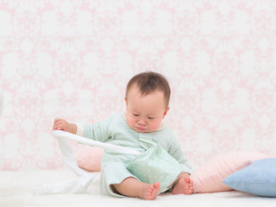 座ってトイレットペーパーを引っ張る赤ちゃんの写真素材 [FYI01914389]