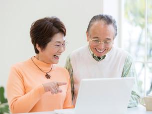 ノートパソコンに向かうシニア夫婦の写真素材 [FYI01914778]