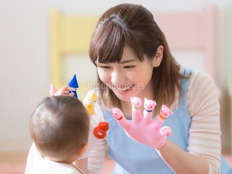 手袋シアターをはめて笑う保育士の写真素材 [FYI01915152]