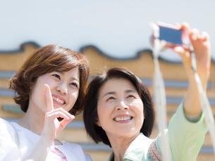 写真撮影をする母と娘の写真素材 [FYI01915236]