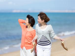 海辺を歩く母と娘の写真素材 [FYI01915580]