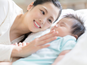 赤ちゃんと添い寝をする母親の写真素材 [FYI01916241]