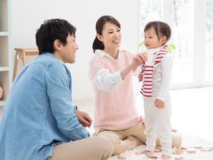 子供の着替えを手伝う夫婦の写真素材 [FYI01916610]