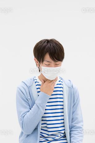 マスクをして喉に手をあてる若者男性の写真素材 [FYI01916777]