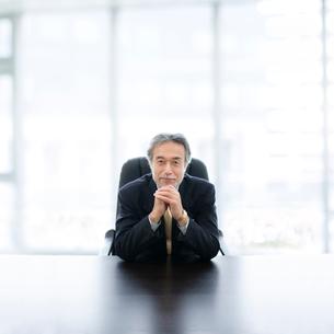机に肘をつくビジネスマンの写真素材 [FYI01916808]