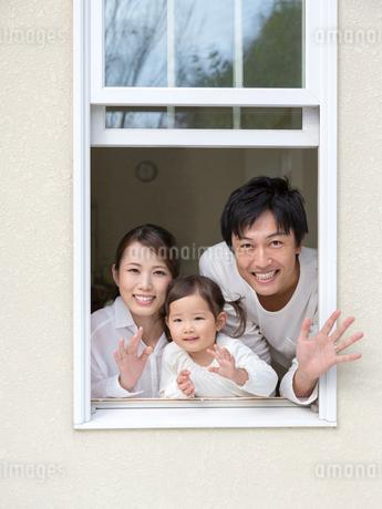 窓から手を振る家族の写真素材 [FYI01916915]