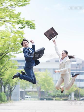 ジャンプをするスーツ姿の男女の写真素材 [FYI01916917]