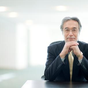 手を組んで微笑むビジネスマンの写真素材 [FYI01916928]