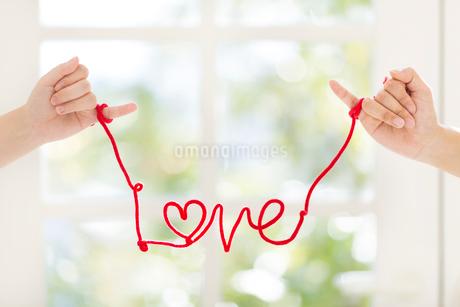 赤いひもを小指に結んだ手の写真素材 [FYI01917051]