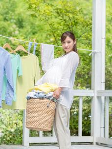 かごに入った洗濯物を持つ妊婦の写真素材 [FYI01917187]