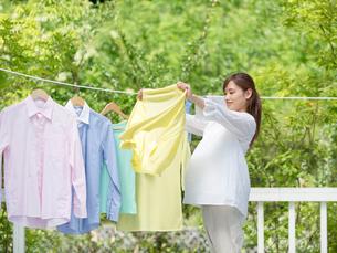洗濯物を広げる妊婦の写真素材 [FYI01917203]