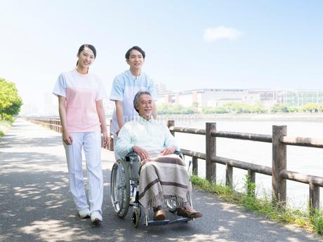 車椅子の患者を押す介護士の写真素材 [FYI01917282]