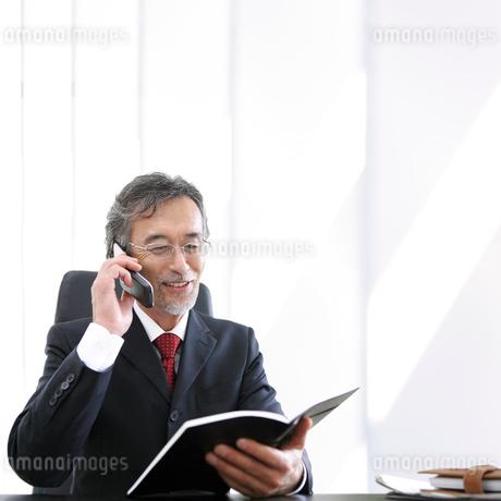 ノートを見ながら通話をするビジネスマンの写真素材 [FYI01917400]
