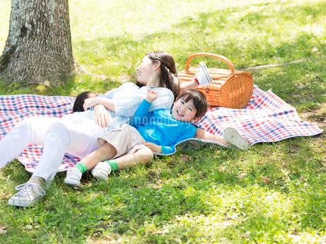 レジャーシートに寝転ぶ母と兄弟の写真素材 [FYI01917465]