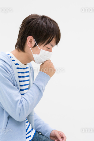 マスクをしてうつむく若者男性の写真素材 [FYI01917585]