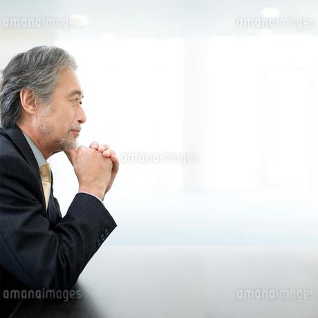 机に肘をつくビジネスマンの写真素材 [FYI01918112]