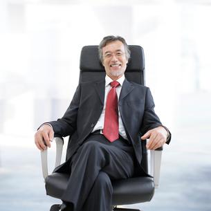 足を組んで椅子に座るビジネスマンの写真素材 [FYI01918247]