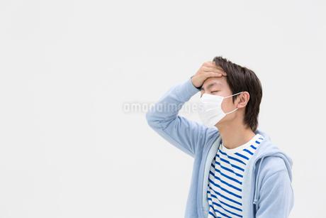 マスクをして額に手をあてる若者男性の写真素材 [FYI01918378]