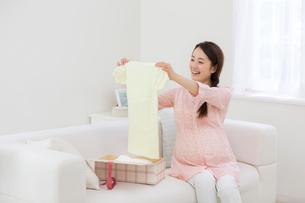 ベビー服を眺める女性の写真素材 [FYI01918461]