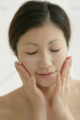 顔に手をあてる女性の写真素材 [FYI01918876]